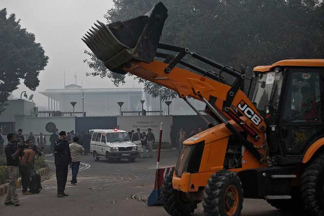 A bulldozer removes the security barriers in front of the U.S. embassy in New Delhi