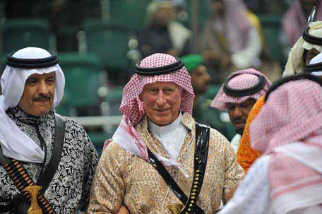 Britain's Prince Charles wears traditional Saudi attire as he dances with Saudi Tourism Minister Salman bin Sultan during the traditional Saudi dancing,known as 'Arda', in Riyadh