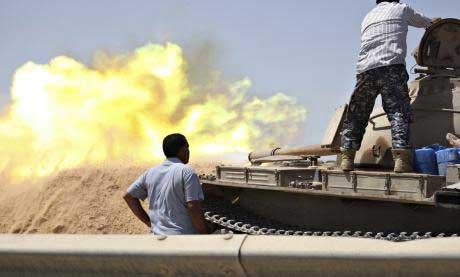 A tank belonging to the Western Shield fires during a clash with rival militias around the former Libyan army camp, Camp 27, in the 27 district, west of Tripoli