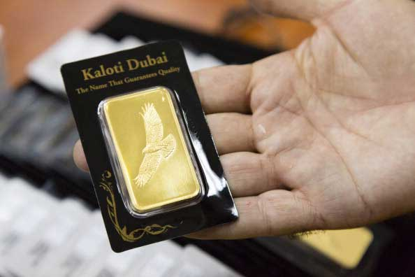 An employee displays a small gold bar in 'Kaloti Dubai' packaging at the Kaloti Jewellery LLC factory in Sharjah, United Arab Emirates, on Sunday, June 30, 2013.