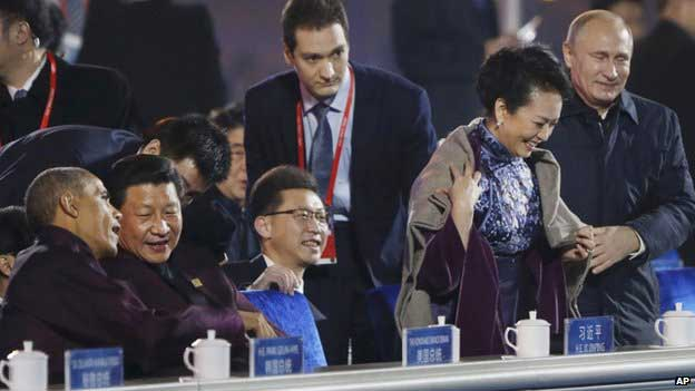 Xi Jingping appears to have no idea a shawl is being placed upon his wife's shoulders