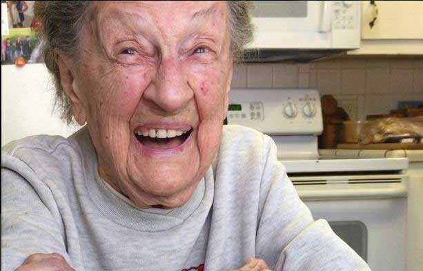 Excited 102 year old spits out her teeth while blowing candles